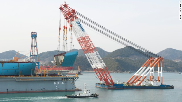 A giant crane lowers a huge section of the first Maersk Triple E into place at the Daewoo Shipbuilding and Marine Engineering shipyard in Okpo, South Korea.