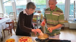 Tenant Dorothea Straube-Koberstein bakes a cake with Christoph Remmlinger, a personal care assistant, at the shared apartment for seniors in Potsdam.