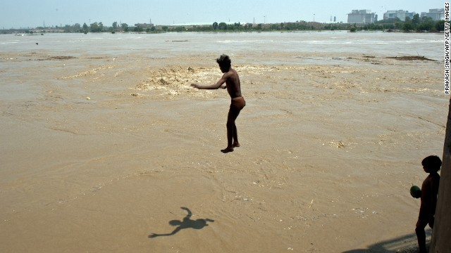 A boy dives into the rising waters of the Yamuna River in New Delhi on Wednesday, June 19. Heavy rains have been lashing parts of north India, as the annual monsoon arrived nearly two weeks ahead of schedule, officials said.