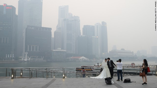 Undeterred by the smog, a couple took engagement photographs in front of the city's skyline at the Marina Bay waterfront on June 20.