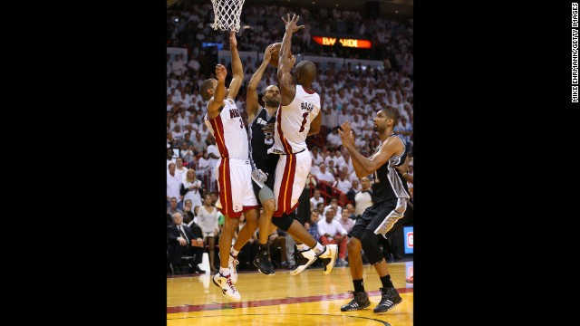 Tony Parker of the San Antonio Spurs drives on Shane Battier and Chris Bosh of the Miami Heat in the fourth quarter.