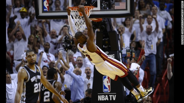 Dwyane Wade of the Miami Heat hangs from the basket after a dunk.