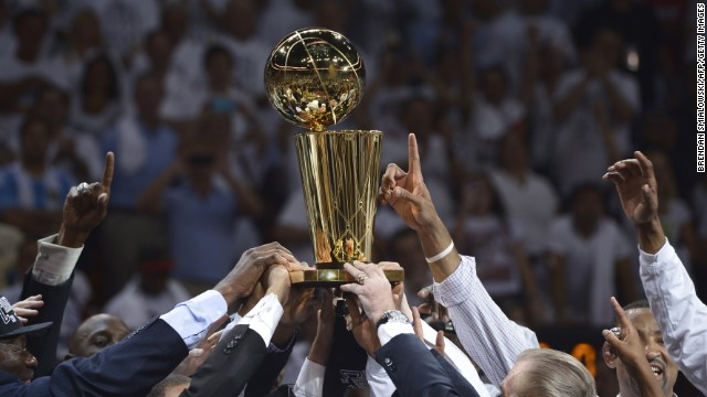 The Heat celebrate their victory, holding the trophy aloft.