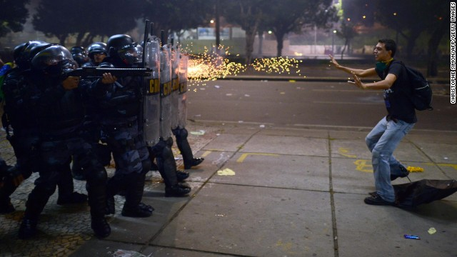 Police fire rubber bullets at a protester during clashes in Rio de Janeiro on Thursday, June 20. Demonstrations in Brazil began in response to <a href='http://www.cnn.com/2013/06/20/world/americas/brazil-protests/?hpt=hp_t2'>plans to increase fares for the public transportation system</a> but have broadened into wider protests over economic and social issues. Since then, both Sao Paulo and Rio de Janeiro have agreed to roll back prices on bus and metro tickets.<!-- --> </br>
