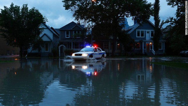 A police car patrols a flooded Calgary neighborhood that was evacuated on June 20.