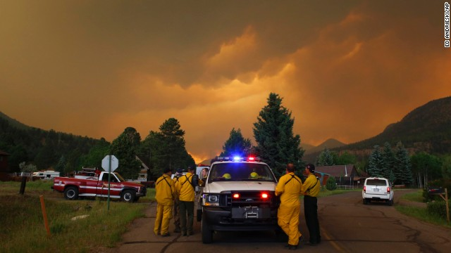 Firefighters monitor a wildfire in a residential area in South Fork on Friday, June 21.