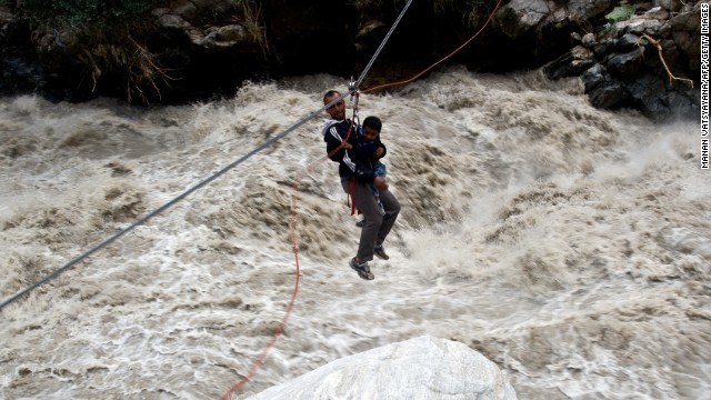 A stranded pilgrim carrying a child is ziplined across a river with the help of Indo-Tibetan Border Police personnel in Govindghat, India, on June 23.