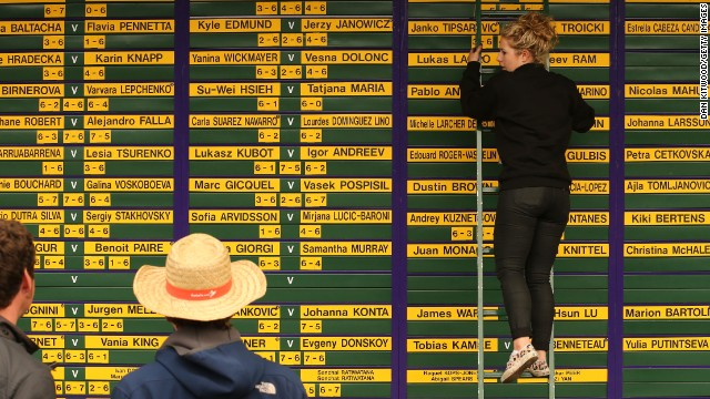A worker updates the Wimbledon scoreboard on June 24.