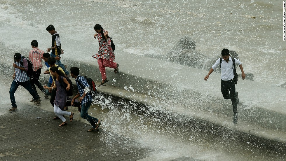 Pedestrians run from water splashing over a sea wall in Mumbai on Monday, June 24. Authorities are scrambling to rescue thousands of people trapped after floods and landslides ravaged north India, leaving up to 1,000 feared dead.