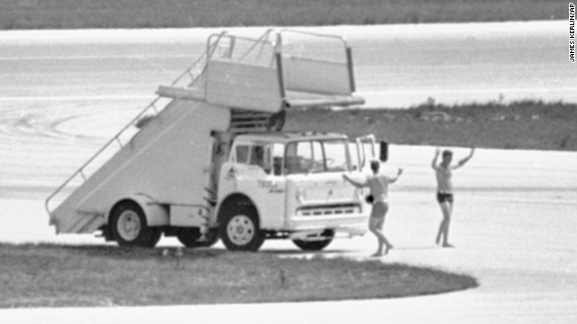 In this July 1972 photo, FBI agents in Miami, wearing only swim trunks, per a hijacker's instructions, prepare to deliver a case containing a $1 million ransom to a hijacked Delta DC8 jet.