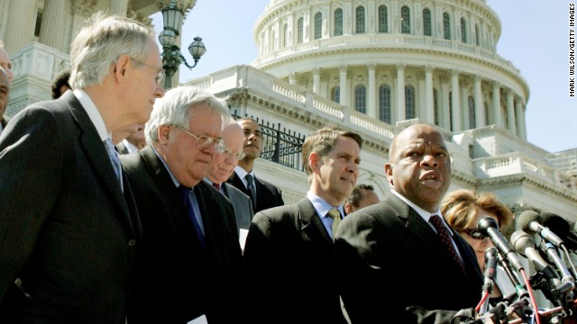 Rep. John Lewis speaks after bipartisan House and Senate officials met to voice support for reauthorizing the Voting Rights Act for an additional 25 years on May 2, 2006. From left, Senate Minority Leader Harry Reid, House Speaker Dennis Hastert, Senate Majority Leader Bill Frist and other officials listen during the media conference.