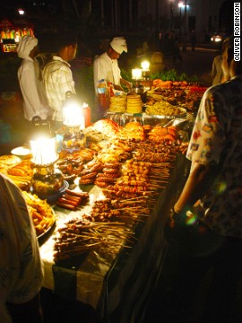 People wander the food stalls at Forodhani Gardens for snacks including Zanzibar pizza, sugarcane drink and fresh seafood.