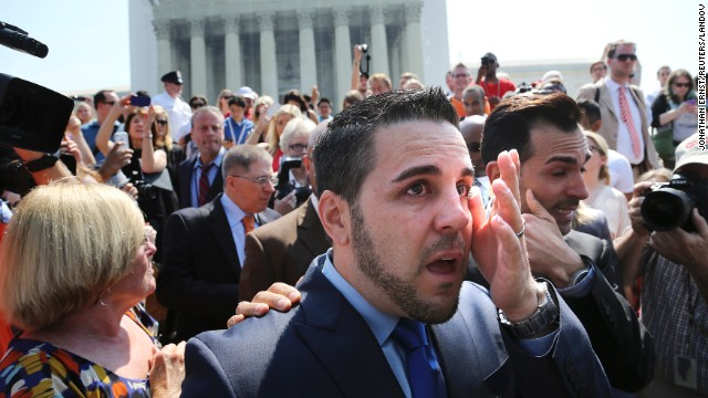 Jeff Zarrillo, center, and Paul Katami, right, plaintiffs in the California case against Proposition 8, wipe away tears after departing the Supreme Court in Washington. Katami proposed to Zarrillo on national news after the ruling.