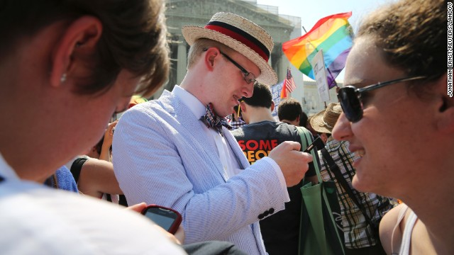 Same-sex marriage proponent Ryan Clarke reads news updates on the rulings outside of the Supreme Court.