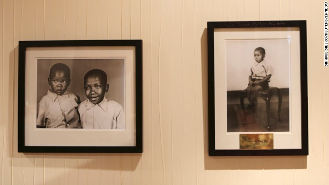 Pictures of the late sons of Nelson Mandela, by photographer Eli Weinberg, hang in his office at the Nelson Mandela Centre of Memory in Houghton, Johannesburg, on Tuesday, June 11. Thembekile Mandela died in a 1969 car accident and Makgatho Mandela died from AIDS in 2005.