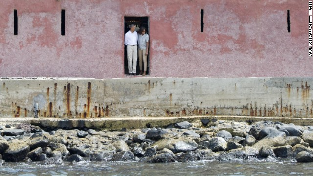 Barack and Michelle Obama look out from the Door of No Return while touring the House of Slaves at Goree Island off the coast of Dakar, Senegal, on Thursday, June 27.