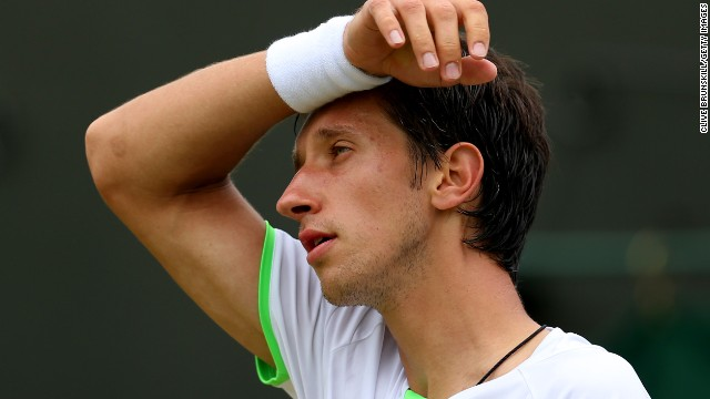 A dejected Sergiy Stakhovsky on his way to defeat against Austria's Jurgen Melzer in their third round match at Wimbledon.