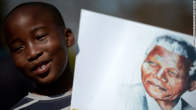 A child holds a portrait of Nelson Mandela outside the Pretoria, South Africa, hospital where Mandela is being treated.
