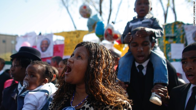Well-wishers sing outside the hospital where former South African President Nelson Mandela is being treated in Pretoria, South Africa, on Sunday, June 30.