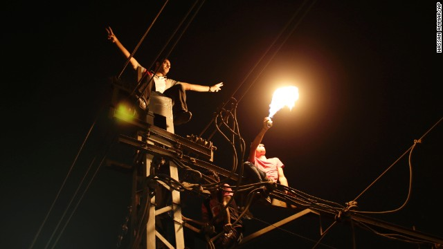 "Protesters sit on top of a power pole as they chant slogans against Morsy outside the presidential palace in Cairo on June 30. ""Egypt is on the brink of a volcano,"" government-run newspaper Al-Akhbar said."