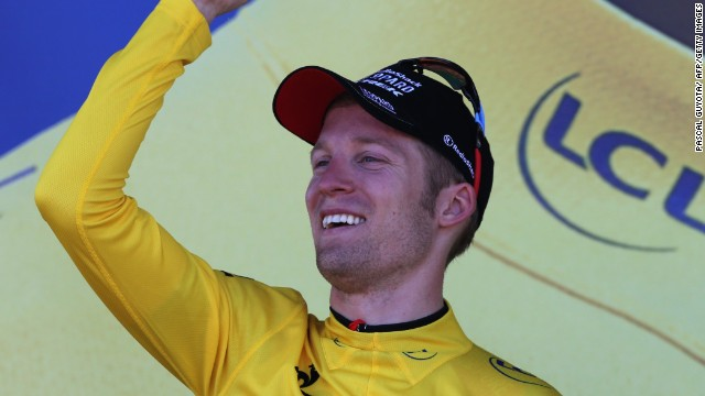 Jan Bakelants dons the yellow jersey after winning the second stage of the Tour de France in Ajaccio.
