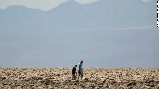 "People walk through the ""Devil's Golf Course"" area of Death Valley, where temperatures were 116 degrees."