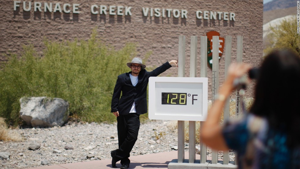 Kevin Martin of Corona, California, poses for a snapshot by an unofficial thermometer at the Furnace Creek Visitor Center in Death Valley National Park on Sunday, June 30. A record-setting and deadly heat wave has spread across the American West.