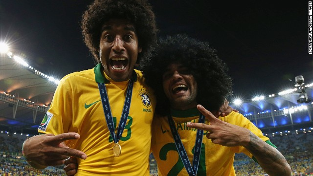 Brazil players Dante, left, and Dani Alves, in a wig, celebrate with their winner's medals.