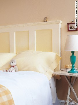 A solid old door, refinished and hung sideways, becomes a perfect -- and perfectly inexpensive -- headboard for a bed.