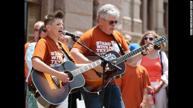 Natalie Maines and her father, Lloyd Maines, play the national anthem at the rally.