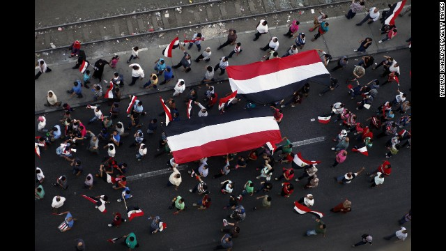 Protesters carry large Egyptian flags while shouting slogans against Morsy and the Muslim Brotherhood outside the presidential place on July 1.