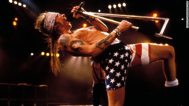 Axl Rose rocks out in flag biker shorts at a '90s Guns 'N Roses show.