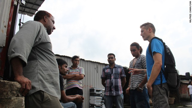 "Cosmo Beatson (far right), executive director of Vision First, a refugee aid organization, gives a pep talk to a group of Bangladeshi refugees in the slum village of Ping Che on June 25, 2013. ""When it dawns on refugees what they're stuck in, they're in shock,"" he says."