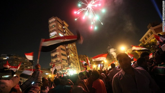 Fireworks go off as protesters gather in the streets outside the presidential palace in Cairo on July 2.