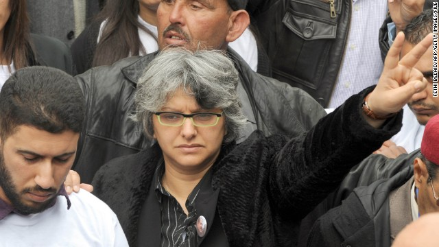 Belaid's widow, Basma Khalfaoui, flashes the sign for victory as Tunisians gather at the tomb of her late husband in Tunis in March. Few Tunisians had probably heard of Khalfaoui before her husband's death, but she has attained rock star status since then.