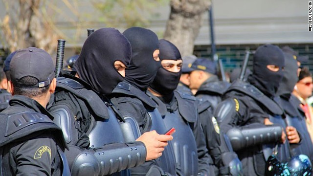 Masked riot police wait for orders as a Tunis square fills with Belaid supporters in March.