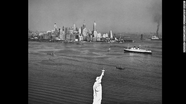 The towering of skyline of downtown Manhattan rises with the Statue of Liberty in the foreground in 1950.
