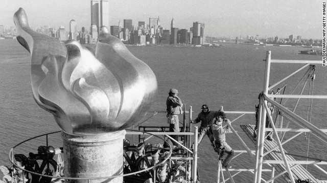 Workers remove scaffolding from around the torch after restoration work in 1985. The twin towers of the World Trade Center can be seen in the background.