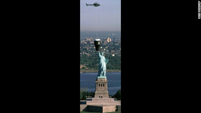 A representation of a giant glass of Guinness is lowered from a helicopter over the Statue of Liberty to publicize the city's first Irish Music & Arts Festival in 1997.