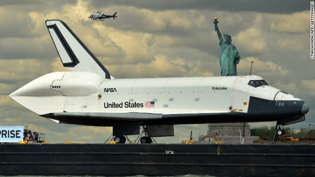 The Space Shuttle Enterprise is towed in June 2012 on a barge past the Statue of Liberty on its way to the Intrepid Sea, Air and Space Museum.