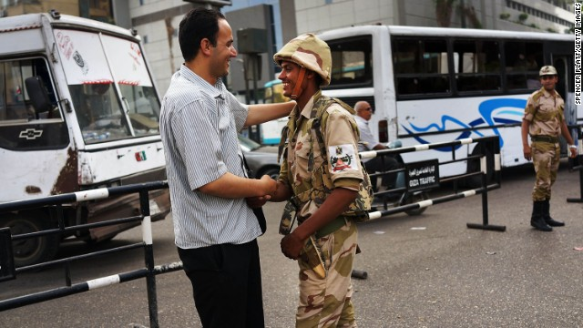 A pedestrian shakes hands with a member of the military at a roadblock in Giza.