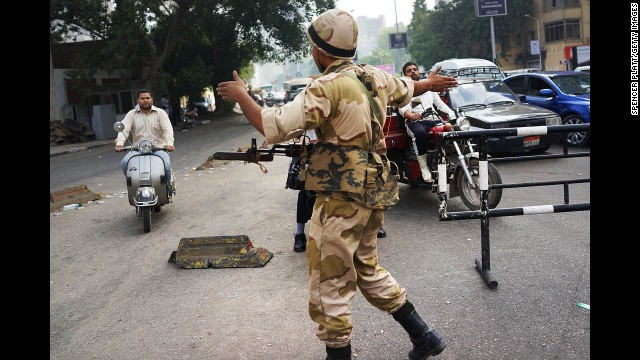 A member of the Egyptian military redirects traffic on July 4 at a roadblock in Giza.