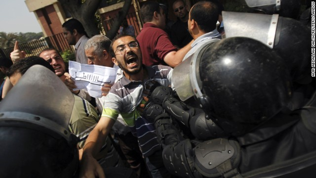 Members of the Muslim Brotherhood and supporters of ousted Egyptian President Mohamed Morsy clash with riot police during the swearing in ceremony of Adly Mansour as interim president in Cairo on Thursday, July 4. Egypt's military deposed Morsy, the country's first democratically elected president, the country's top general announced Wednesday. <a href='http://www.cnn.com/2013/07/04/middleeast/gallery/egypt-after-coup/index.html'>View photos of Egypt after the coup.</a>