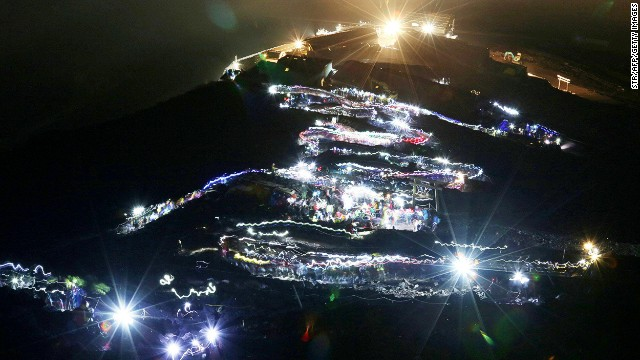 Climbers create a snaking queue of flashlights as they walk the path up the mountain.