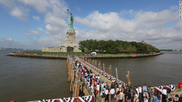 Visitors to the Statue of Liberty disembark from the first ferry to leave Manhattan, on Thursday, July 4, the first day the attraction reopened after suffering damage from Superstorm Sandy.