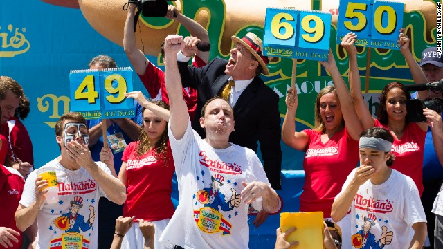 Perennial chomping champ Joey Chestnut, center, wins New York's annual Independence Day hot dog eating competition yet again with a total of 69 hot dogs and buns on Thursday at Coney Island in Brooklyn.