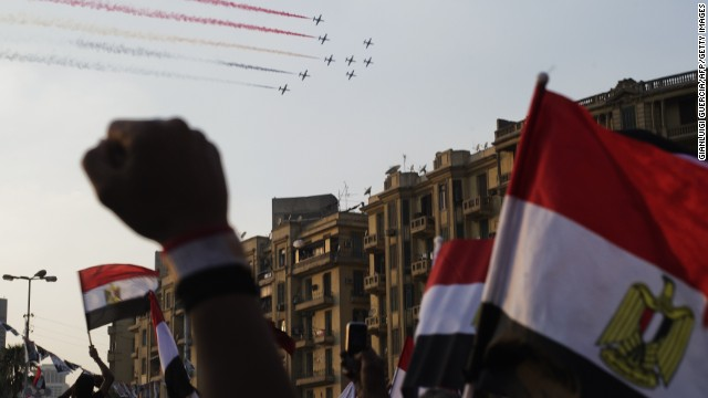 Egyptians cheer and wave national flags as airplanes fly above Tahrir Square on July 4, leaving a trail of smoke in the colors of the national flag.