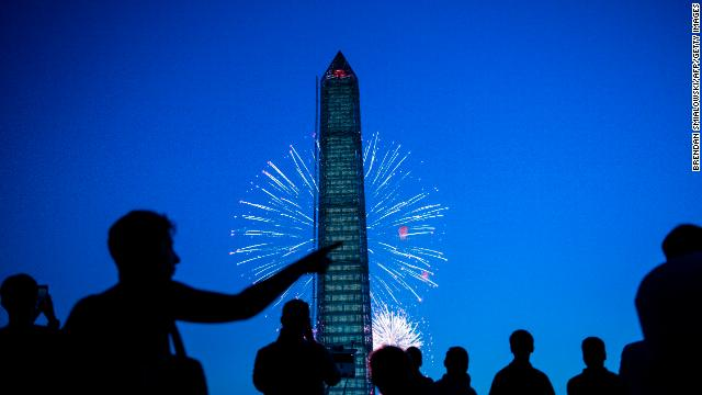 People watch fireworks burst behind the Washington Monument on the National Mall in Washington last year.