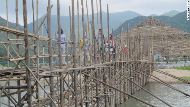 Tourists cross the newly built footbridge next to a wooden framed event center.