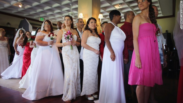 Brides line up with their husbands to be during a group Valentine's day wedding at the National Croquet Center on February 14, 2013 in West Palm Beach, Florida. The group wedding ceremony is put on by the Palm Beach Country Clerk & Comptroller's office and approximately 40 couples tied the knot.